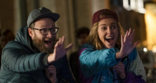 Seth Rogen and Charlize Theron Smile and wave high, the two dressed in silly looking street attire