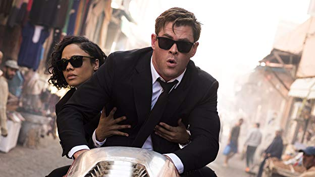Men in Black International agents M and H riding a hover cycle through a city.