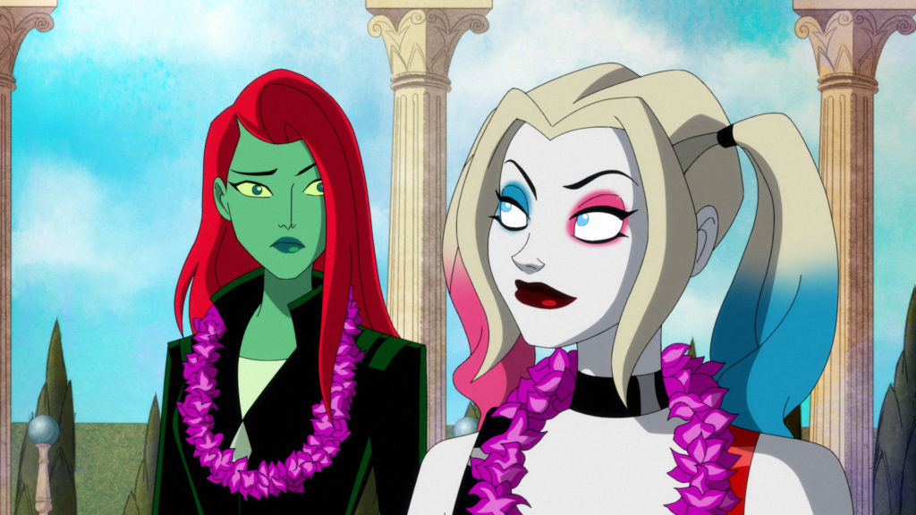 Harley Quinn looks at Poison Ivy in Themyscira. They are both wearing leis.