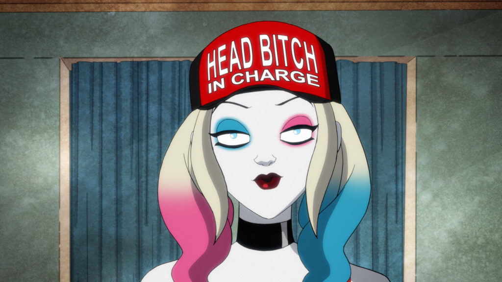 Harley Quinn wearing a red hat that says Head Bitch in Charge.