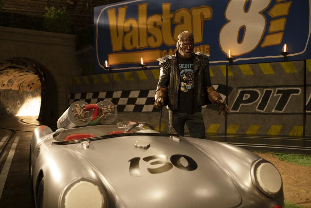Riley Shanahan as Cliff Steele next to a race car.