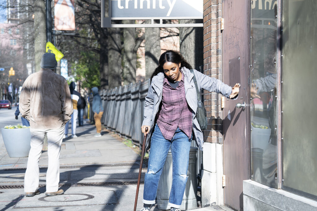 Karen Obilom as Roni Evers, walking with a cane to open a door.