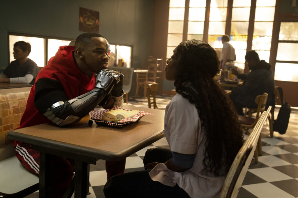 Left to Right: Joivan Wade as Vic Stone/Cyborg and Karen Obilom as Roni Evers having lunch at a sub shop.