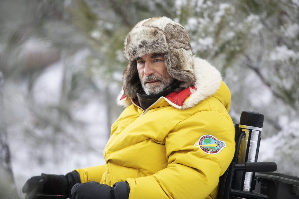 Niles Caulder dressed for intense cold in his wheelchair in a snowy forest.