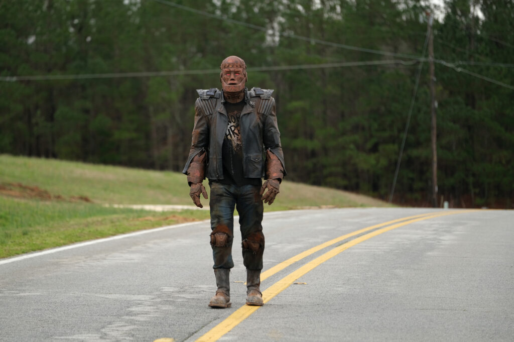 Cliff (Riley Shanahan) is walking in the middle of the road in the middle of the country.