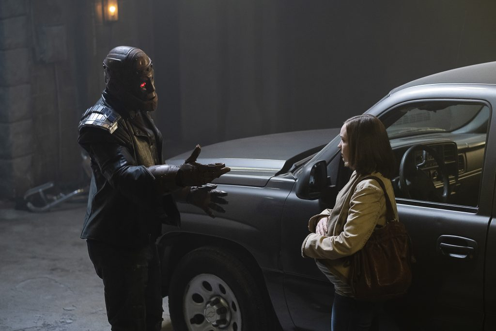 Left to Right: Cliff talking to his pregnant daughter, Clara, in front of a car in a garage.