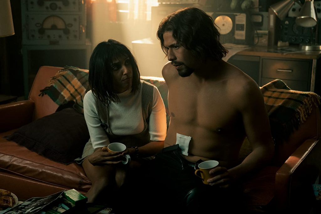 Lily with a cup in hand and Diego, shirtless, also with a cup in hand. Both listening to Five's plan.